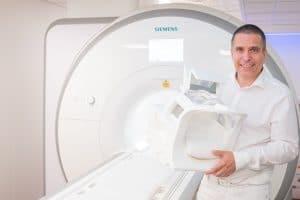 Dr. Lins zeigt das MRT und eine Kopfspule